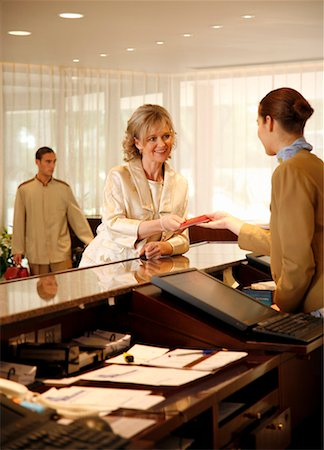 Woman checking in at the hotel reception desk Stock Photo - Premium Royalty-Free, Code: 644-01437380