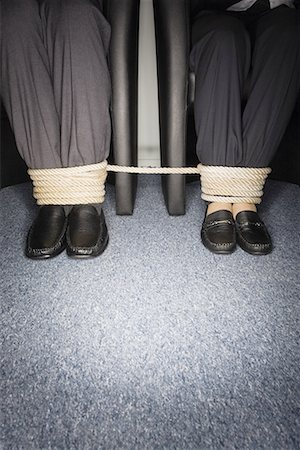 Male and female business people's legs tied Stock Photo - Premium Royalty-Free, Code: 644-01630905