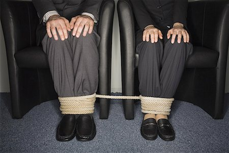 Male and female business people's legs tied Stock Photo - Premium Royalty-Free, Code: 644-01630906