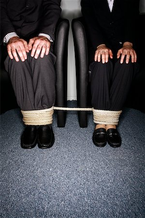Male and female business people's legs tied Stock Photo - Premium Royalty-Free, Code: 644-01630946