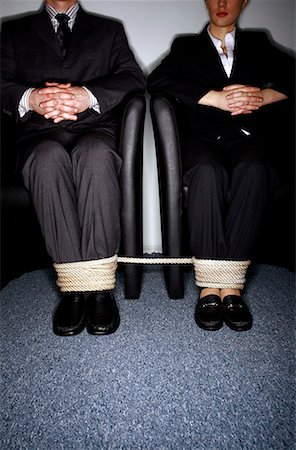 Male and female business people's legs tied Stock Photo - Premium Royalty-Free, Code: 644-01630947