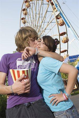 Teenage couple in front of Ferris wheel in amusement park Stock Photo - Premium Royalty-Free, Code: 644-01825537