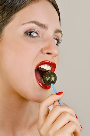 picture of a red lollipop - Female young adult biting a lollipop Stock Photo - Premium Royalty-Free, Code: 644-02153078
