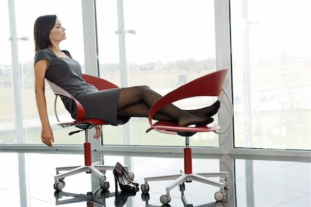 Professional woman resting her legs up on office chair Stock Photo - Premium Royalty-Free, Code: 644-02922965