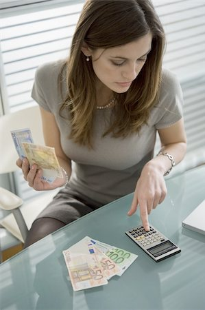 Professional woman adding up euro bills with calculator Stock Photo - Premium Royalty-Free, Code: 644-02923014