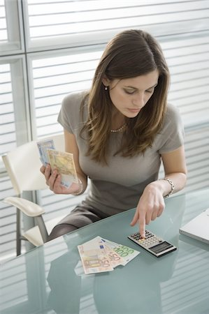 Professional woman adding up euro bills with calculator Stock Photo - Premium Royalty-Free, Code: 644-02923015