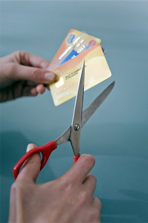 Hands cutting credit cards with scissors Stock Photo - Premium Royalty-Free, Code: 644-02923010