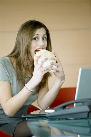secretary desk - Businesswoman eating pita sandwich at desk Stock Photo - Premium Royalty-Free, Code: 644-02923289
