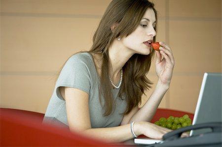 secretary desk - Businesswoman eating a strawberry at laptop Stock Photo - Premium Royalty-Free, Code: 644-02923292