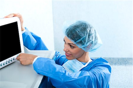 Surgeon adjusting monitor in operating room Stock Photo - Premium Royalty-Free, Code: 644-03659484