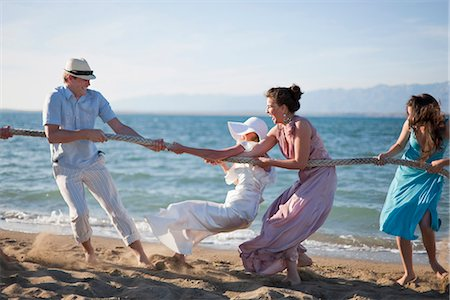 Newlyweds and guests playing tug of war Stock Photo - Premium Royalty-Free, Code: 649-04248555
