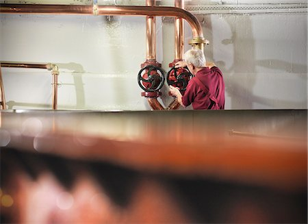 Worker turning valves in distillery Fotografie stock - Premium Royalty-Free, Codice: 649-04248745