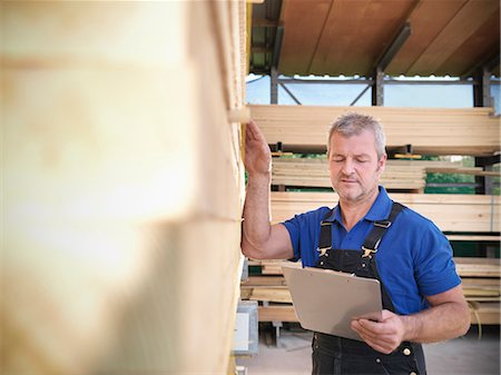 Worker checking wooden planks in joinery Stock Photo - Premium Royalty-Free, Code: 649-04248814