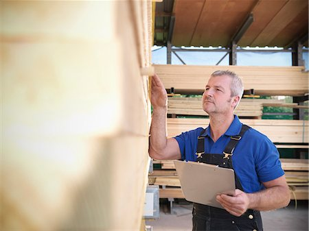 Worker checking wooden planks in joinery Stock Photo - Premium Royalty-Free, Code: 649-04248815