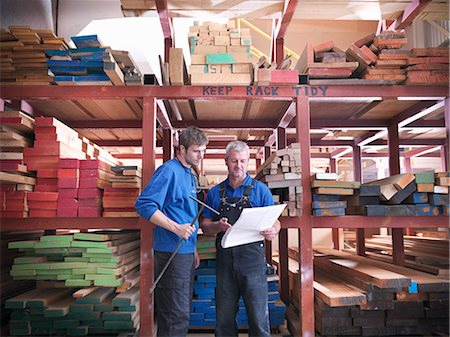 Workers reading together in joinery Stock Photo - Premium Royalty-Free, Code: 649-04248834