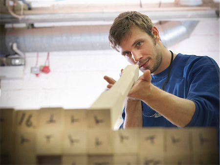 Worker examining wood in joinery Stock Photo - Premium Royalty-Free, Code: 649-04248830