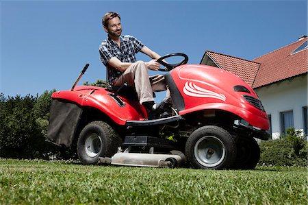 Man riding lawn mower in backyard Stock Photo - Premium Royalty-Free, Code: 649-04827412