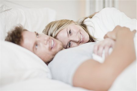 Smiling couple relaxing in bed Stock Photo - Premium Royalty-Free, Code: 649-04827564