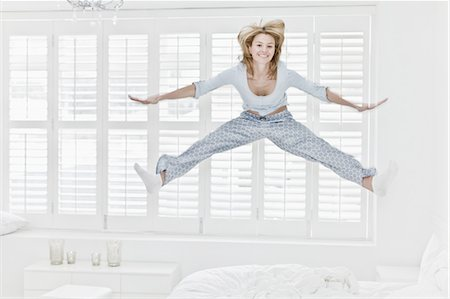 Woman jumping on bed Stock Photo - Premium Royalty-Free, Code: 649-04827577