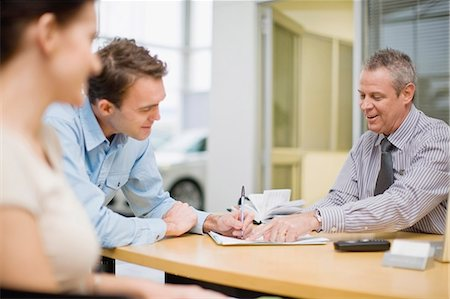 Couple signing papers with car salesman Stock Photo - Premium Royalty-Free, Code: 649-05521317