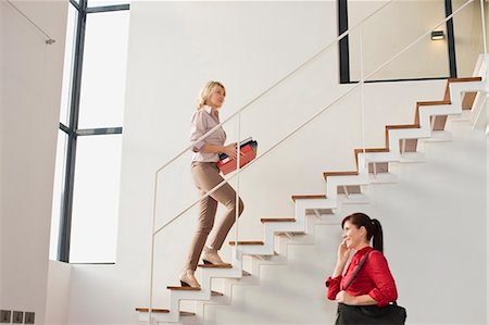 Businesswoman climbing stairs in office Stock Photo - Premium Royalty-Free, Code: 649-05521387