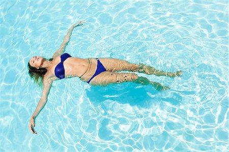 sexi women full body - Woman floating in swimming pool Stock Photo - Premium Royalty-Free, Code: 649-05521415