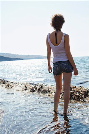 Woman standing in waves on beach Stock Photo - Premium Royalty-Free, Code: 649-05521442