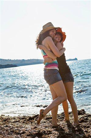 Women in sunhats hugging on beach Stock Photo - Premium Royalty-Free, Code: 649-05521457