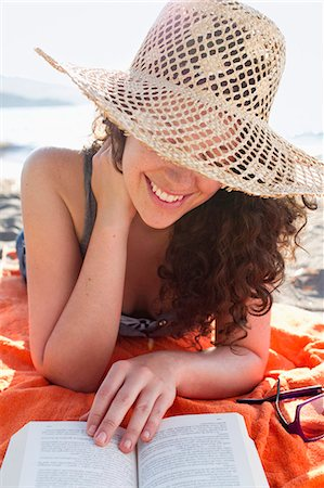 Smiling woman reading on beach Stock Photo - Premium Royalty-Free, Code: 649-05521465