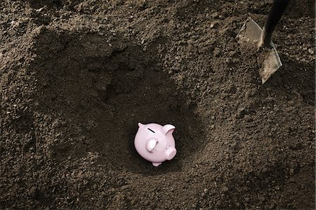 dirt - Shovel digging up piggy bank Stock Photo - Premium Royalty-Free, Code: 649-05521510