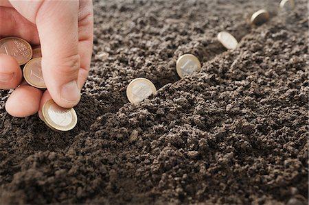 Man planting Euro coins in soil Stock Photo - Premium Royalty-Free, Code: 649-05521511