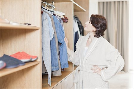 Woman picking clothes out of closet Stock Photo - Premium Royalty-Free, Code: 649-05521576