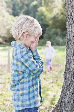 Children playing hide and seek outdoors Stock Photo - Premium Royalty-Free, Code: 649-05521665