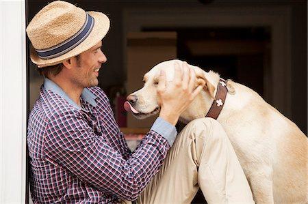 dog lick - Man petting dog in window Stock Photo - Premium Royalty-Free, Code: 649-05522149