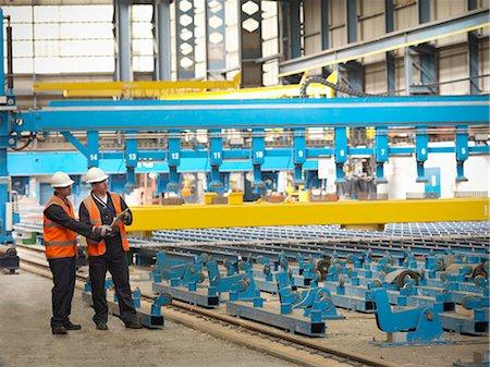 Workers examining shipbuilding machinery Stock Photo - Premium Royalty-Free, Code: 649-05522235
