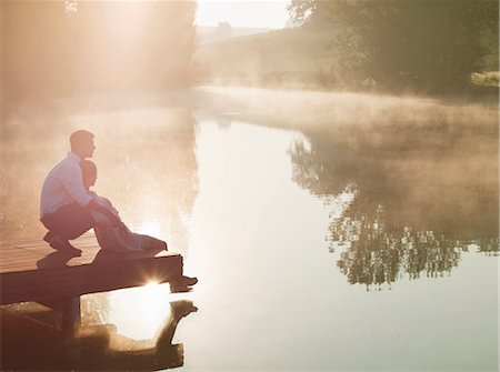 Couple relaxing on dock of lake Stock Photo - Premium Royalty-Free, Code: 649-05522356