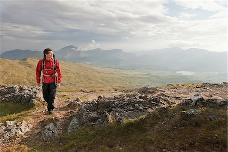 Hiker walking on rocky mountaintop Stock Photo - Premium Royalty-Free, Code: 649-05522376