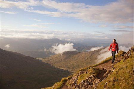 Hiker walking on rocky mountaintop Stock Photo - Premium Royalty-Free, Code: 649-05522394