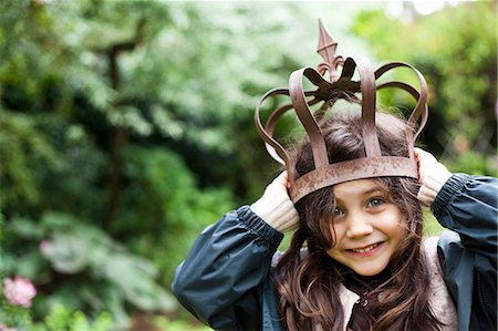 Girl playing with metal crown outdoors Stock Photo - Premium Royalty-Free, Code: 649-05555569