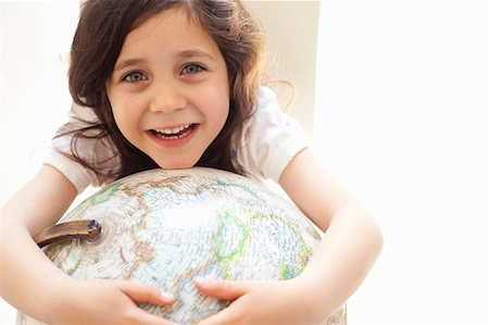 education concept - Smiling girl hugging globe indoors Stock Photo - Premium Royalty-Free, Code: 649-05555577