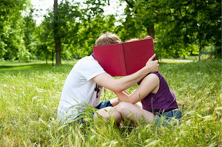 Teenagers hiding behind book in park Stock Photo - Premium Royalty-Free, Code: 649-05555613