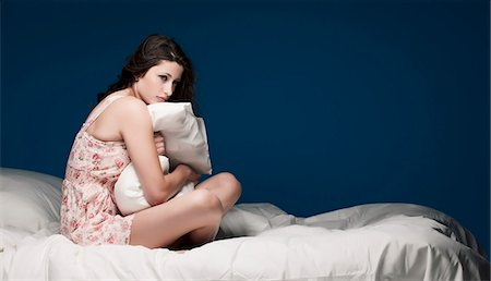 Teenage girl hugging pillow on bed Stock Photo - Premium Royalty-Free, Code: 649-05555639