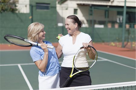 Older women hugging on tennis court Stock Photo - Premium Royalty-Free, Code: 649-05555774