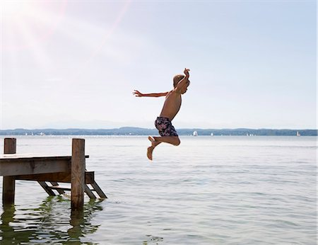 Boy jumping into lake from dock Stock Photo - Premium Royalty-Free, Code: 649-05556067