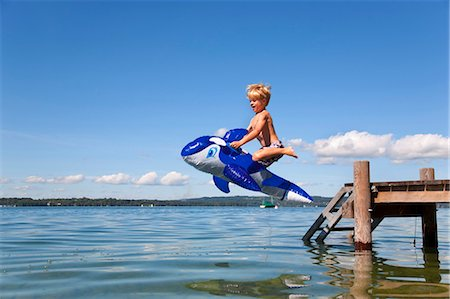 Boy jumping into lake with toy whale Stock Photo - Premium Royalty-Free, Code: 649-05556079