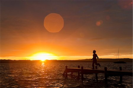 release - Boy running on wooden dock at sunset Stock Photo - Premium Royalty-Free, Code: 649-05556117