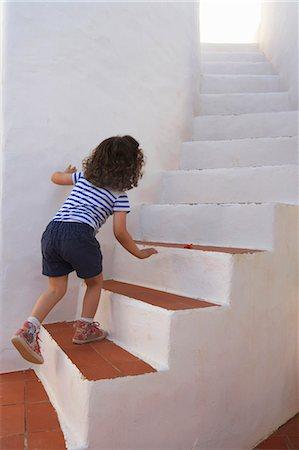Girl carefully climbing steps Stock Photo - Premium Royalty-Free, Code: 649-05556363