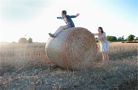 roll (people and animals rolling around) - Girls playing on hay bale in field Stock Photo - Premium Royalty-Free, Code: 649-05556619