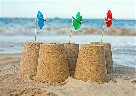 five - Sandcastles with pinwheels on beach Stock Photo - Premium Royalty-Free, Code: 649-05648750