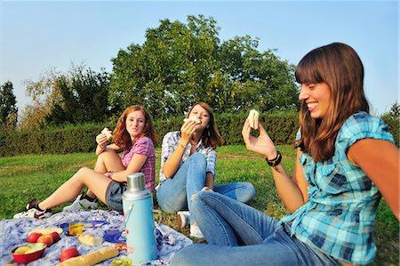 Teenage girls picnicking in rural field Stock Photo - Premium Royalty-Free, Code: 649-05648922